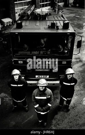 Fire fighters from West Midlands Fire Brigade stand proudly in front of a fire engine in Dudley - Stock Photo