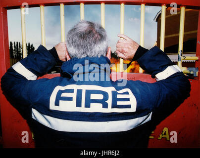Officer from West Midlands Fire Brigade watches a fire in West Midlands - Stock Photo