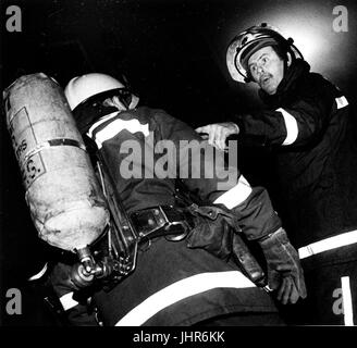 Station officer from West Midlands Fire Brigade gives orders to fire fighter about to enter burning building in - Stock Photo