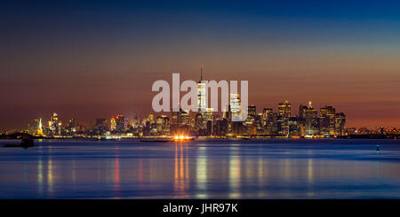First light of the day on Lower Manhattan skyscrapers from New York City Harbor. Financial District and Midtown - Stock Photo