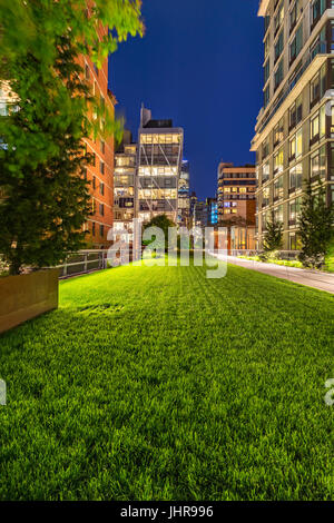 Highline promenade at twilight with illuminated high-rises in Chelsea. Manhattan, New York City Stock Photo