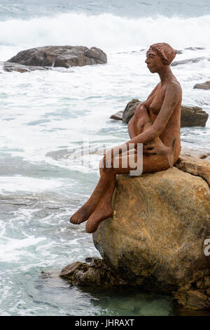 Crashing waves head towards Layla, a public art sculpture on a coastal rock near the mouth of the Margaret River, - Stock Photo