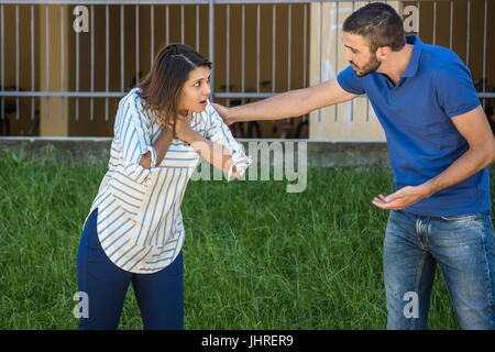 guy making the heimlich maneuver to a girl while she's choking - Stock Photo