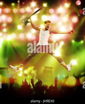 Young and handsome guitarist jumping on the stage - Stock Photo