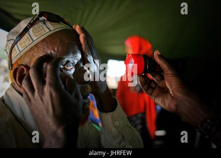 An elderly Somalian man undergoes an eye examination at a Ugandan ophthalmic clinic inside a tent at the Qatar internally - Stock Photo