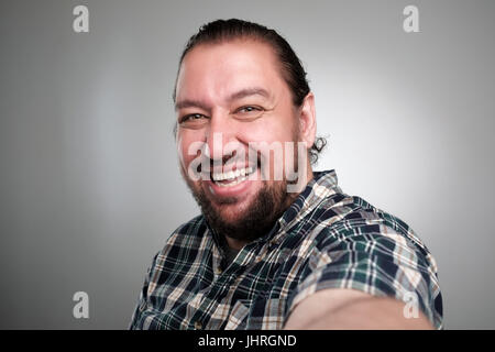 Beautiful young man in casual clothes make selfie on a gray background. He has a happy face, smiling with teeth. - Stock Photo