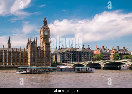 Tourists aboard a floating river restaurant on the river Thames outside the Houses of Parliament, Westminster, London, - Stock Photo