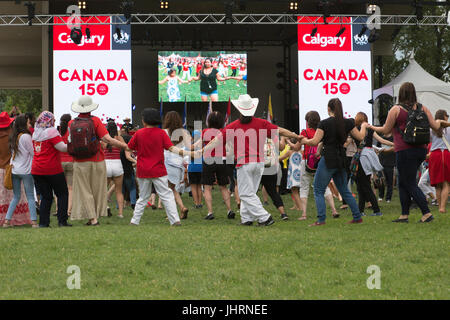 Round dance with audience participation during Canada Day powwow in Prince's Island Park celebrating Canada's 150th - Stock Photo