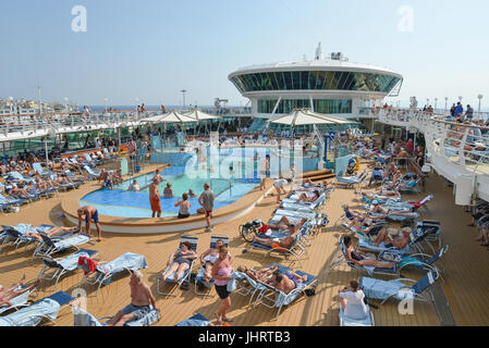 Crowded pool deck on Royal Caribbean 'Grandeur of the Seas' cruise ship, Chora, Mykonos, Cyclades, South Aegean - Stock Photo