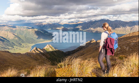 Female hiker looking at lake, Lake Hawea and mountain landscape, Isthmus Peak, Otago, South Island, New Zealand - Stock Photo