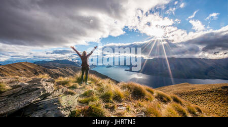 Hiker stretching arms in the air, sun shining, Lake Wanaka and mountain landscape, Isthmus Peak, Otago, South Island - Stock Photo