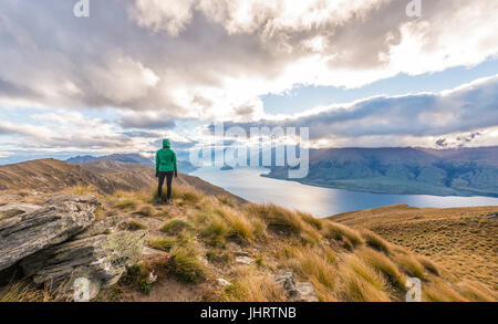 Female hiker woman looking at lake, Lake Hawea and mountain landscape, Isthmus Peak, Otago, South Island, New Zealand - Stock Photo