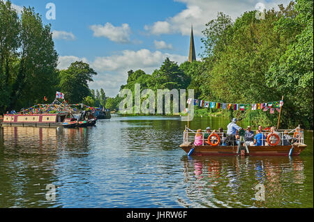 Stratford upon Avon and the old chain ferry, decked in bunting crosses the River Avon during the river festival. - Stock Photo
