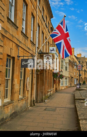 Chipping Campden High Street and a Union Jack flag flying from the from of a stone building in the Cotswold market - Stock Photo