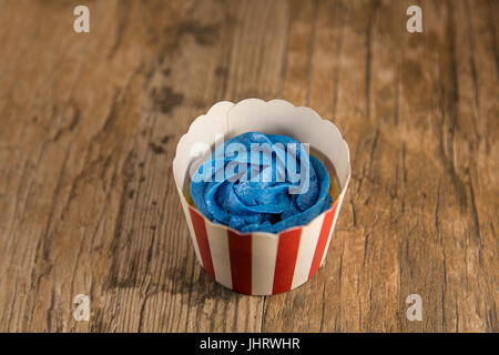 Cupcake with blue frosting in Fourth of July cup. Shallow depth of field. - Stock Photo