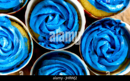 Cupcakes with blue frosting and Fourth of July cups. Shallow depth of field. - Stock Photo