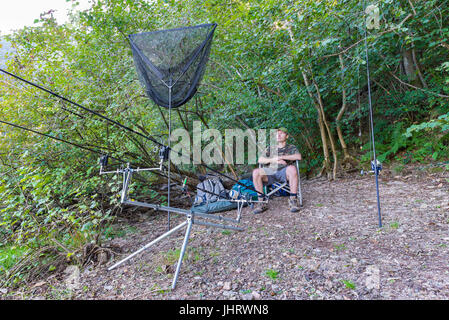 Fishing adventures, carp fishing. Fisherman, on the shore of a lake, relaxes while waiting to catch a fish with - Stock Photo