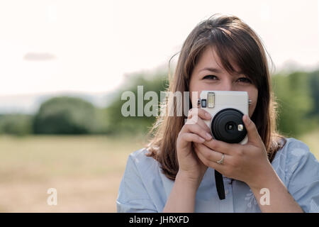 Lovely young long-haired girl with instant camera. - Stock Photo