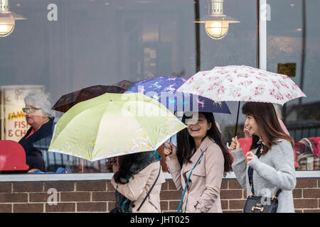 Blackpool, Lancashire, 15th July 2017. UK Weather.  Heavy rain downpours soak the shoppers as they head into Blackpool - Stock Photo