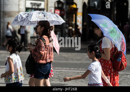 Madrid, Spain. 14th July 2017. Tourists with umbrellas  walk in Puerta del Sol during a heat wave. Spain is under - Stock Photo