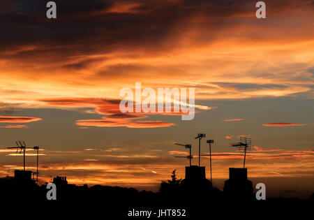 North London, UK. 15th July, 2017: Silhouettes of chimneys at golden and colourful sunset over north London. Credit: - Stock Photo