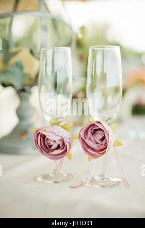 Two glasses for newlyweds bride decorated with beautiful roses stand on the table at wedding celebration. Close - Stock Photo