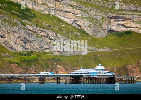 A summers day over both the Great Orme limestone rock formation and the Pier beneath it at the popular seaside resort - Stock Photo