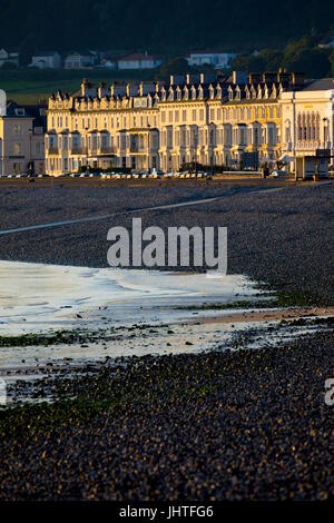 An early sunrise illuminating the many guest houses, hotels and b&b's on the seafront promenade at the popular seaside - Stock Photo