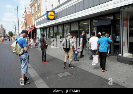 Customers waiting on Walthamstow High Street for Lidl supermarket store to open in the morning  East London E17 - Stock Photo