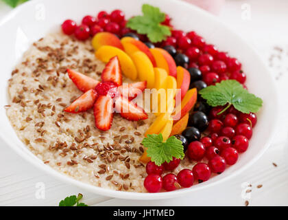 Tasty and healthy oatmeal porridge with berry, flax seeds and smoothies. Healthy breakfast. Fitness food. Proper - Stock Photo