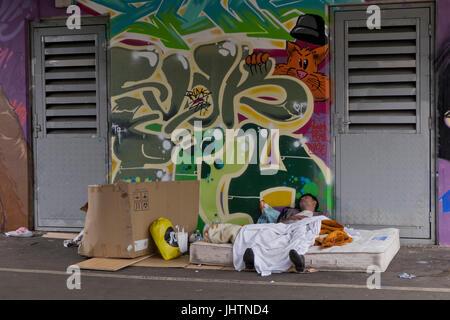 Young homeless man sleeping under railway bridge with graffiti art in Shoreditch, Brick Lane. London.UK - Stock Photo