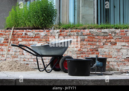 A wheelbarrow, a professional hand mixer, cement mortars and shovels stand on the construction site for the restoration - Stock Photo