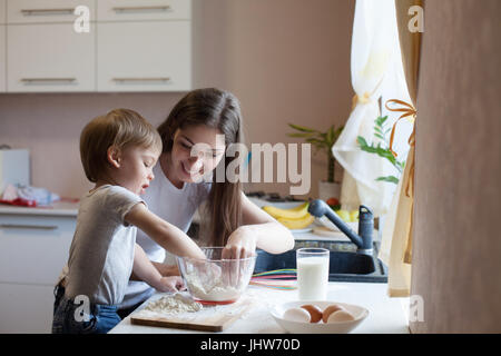 mother and son prepare pie with flour - Stock Photo