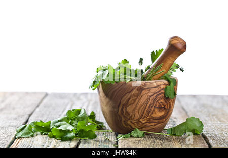 Different herbs on a old wooden table . Wooden mortar with rosemary, coriander, thyme and parsley.Isolated on white - Stock Photo
