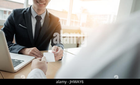 young businessman at the hiring interview in the office, meeting at office lobby, changing business cards - Stock Photo