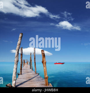 Wooden pier on a tropical island, sea and blue sky - Stock Photo