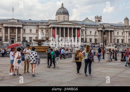 Tourists and locals standing and sitting outside the National Gallery on Trafalgar Square, London,  Relaxing, chatting, - Stock Photo