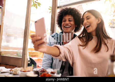 Young couple sitting in the cafe and taking selfie with smart phone. Beautiful woman taking self portrait with her - Stock Photo
