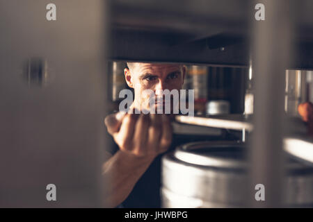 Man working in brewery factory. Employee of production line putting aluminum keg on filling line. - Stock Photo