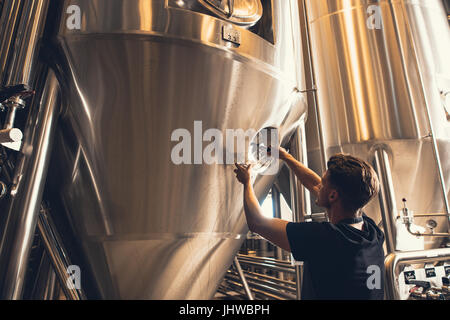 Young man working in beer manufacturing factory. Brewer working with industrial equipment at the brewery. - Stock Photo