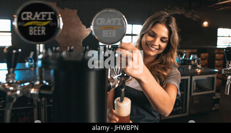 Beautiful young woman pouring beer into the glass. Female bartender tapping craft beer in bar. - Stock Photo