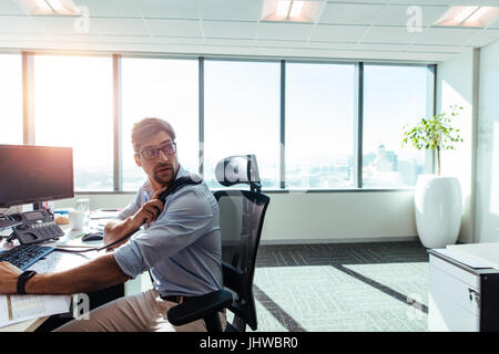 Businessman working in his office with computers and business papers on table. Young entrepreneur looking behind - Stock Photo