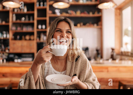 Portrait of beautiful young woman standing in a cafe and drinking coffee. Smiling young female having coffee in - Stock Photo