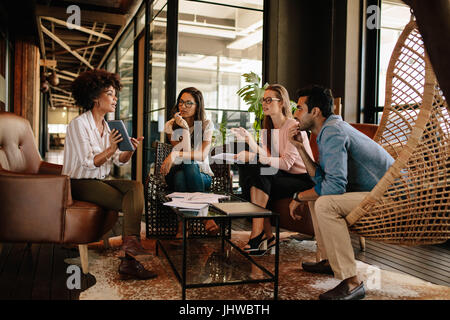 Shot of young woman giving presentation to colleagues at office. Creative business team during meeting. - Stock Photo