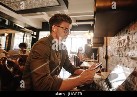Handsome young man sitting at cafe with laptop and using smart phone. Casual businessman reading text message on - Stock Photo