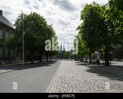 View along Munkegata to Nidarosdomen Cathedral with Stiftsgarden The Royal Residence on the left side with statue - Stock Photo