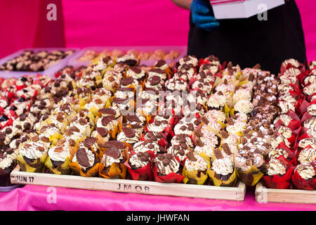 Cream and chocolate cupcakes for sale at the farmers market, cakes for sale, cake sale abundance, tasty, spoilt - Stock Photo