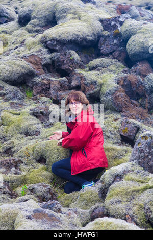 Female tourist amazed at the thickness of moss growing on the Eldhraun Lava Field in Iceland - Stock Photo