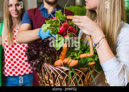 The seller and two girls with a basket of vegetables. Girlfriends buy vegetables on the market. - Stock Photo