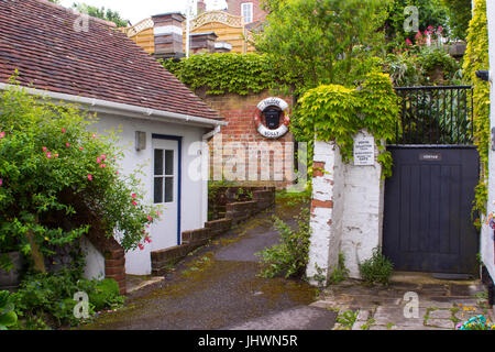A leafy lane near the harbour in Lymington, Hampshire on the south coast of England with cottage and gardens with - Stock Photo
